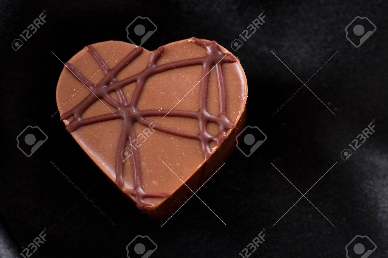 almond cream heart shaped chocolate on a dark silk Stock Photo - 17445901