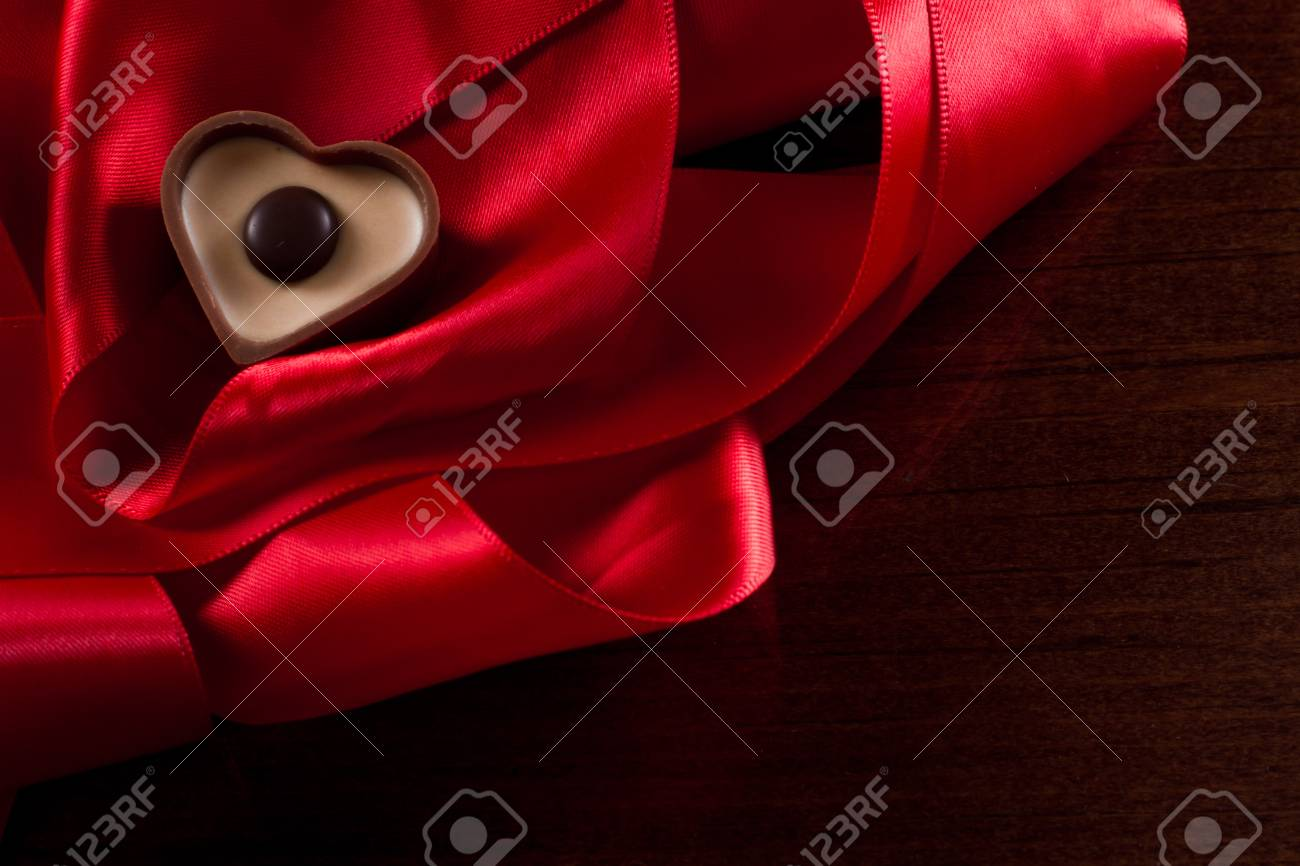 heart shaped milk chocolate with caramel cream on a red silk fading into a black background Stock Photo - 17445909