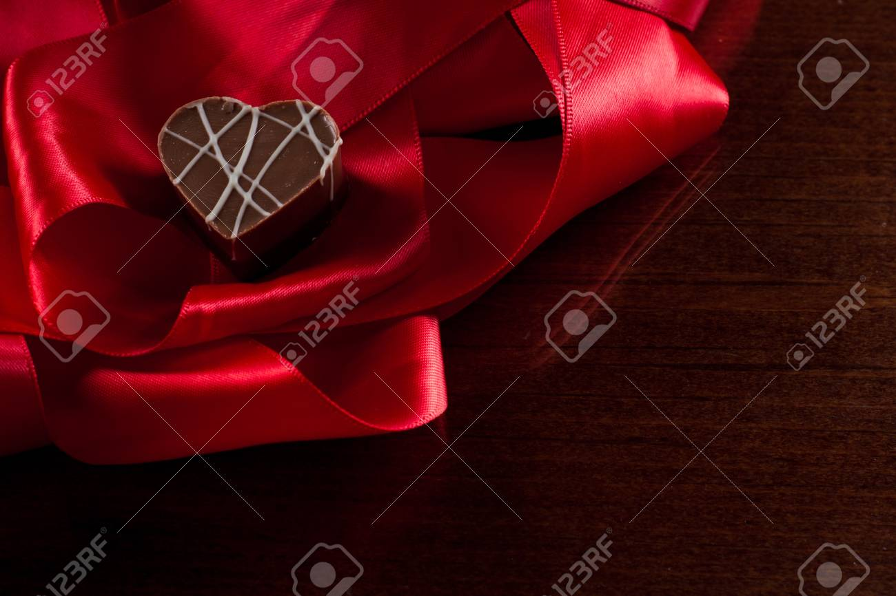 heart shaped chocolate hazelnut with cream and toffee on a red silk fading in to black Stock Photo - 17445920