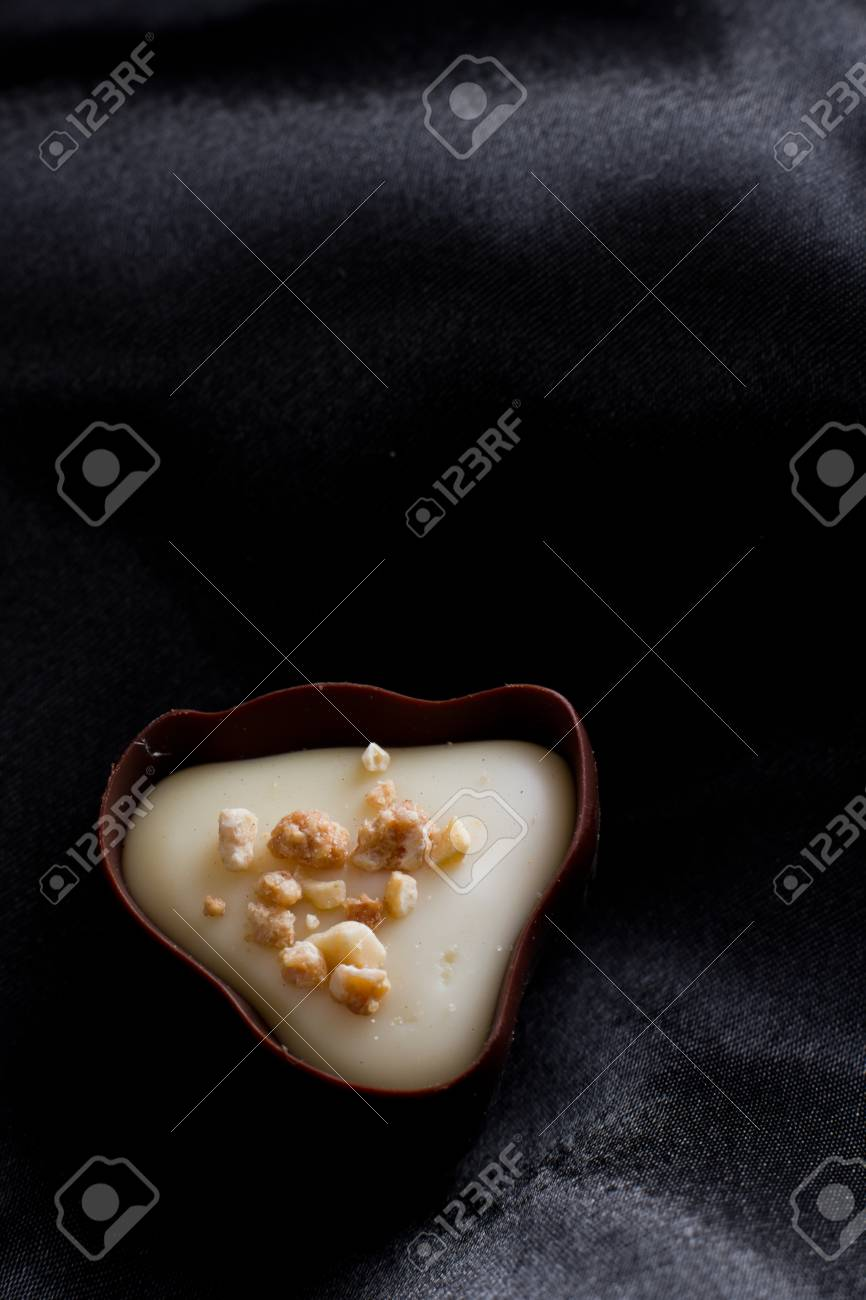 hand crafted chocolate dessert cups with praline filling on a dark silk background Stock Photo - 17439327