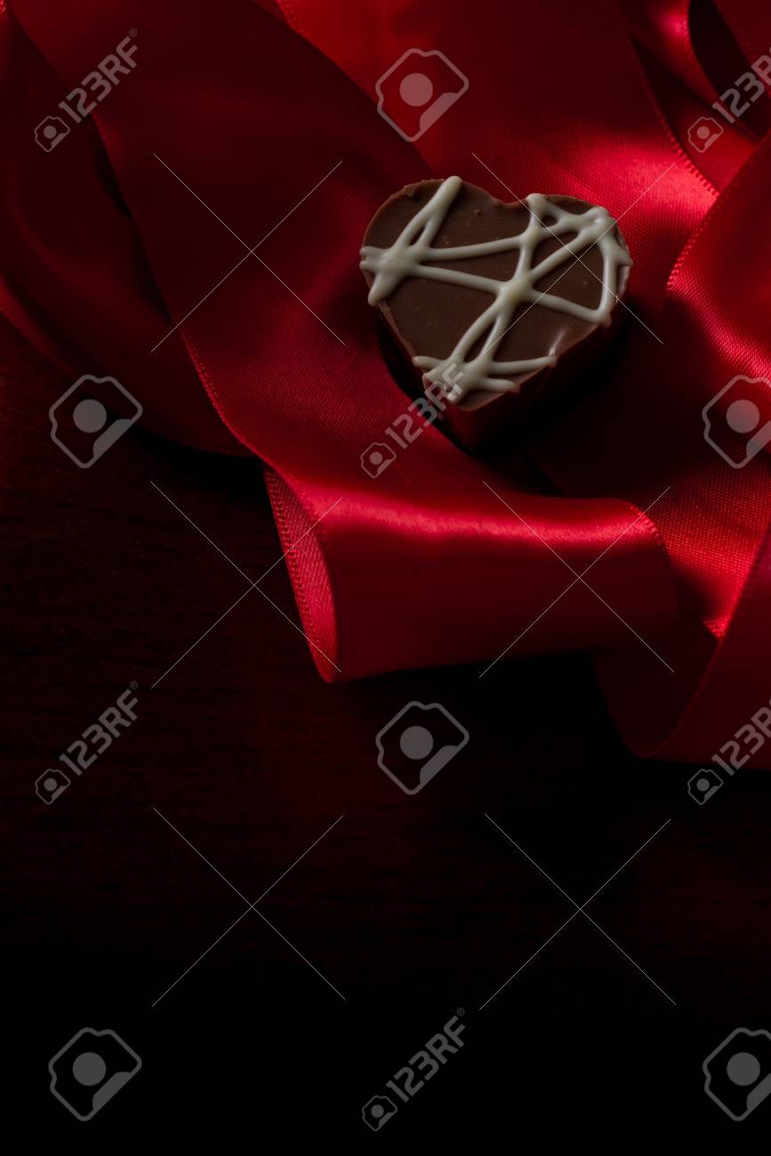 heart shaped chocolate hazelnut with cream and toffee on a red silk fading in to black Stock Photo - 17439330