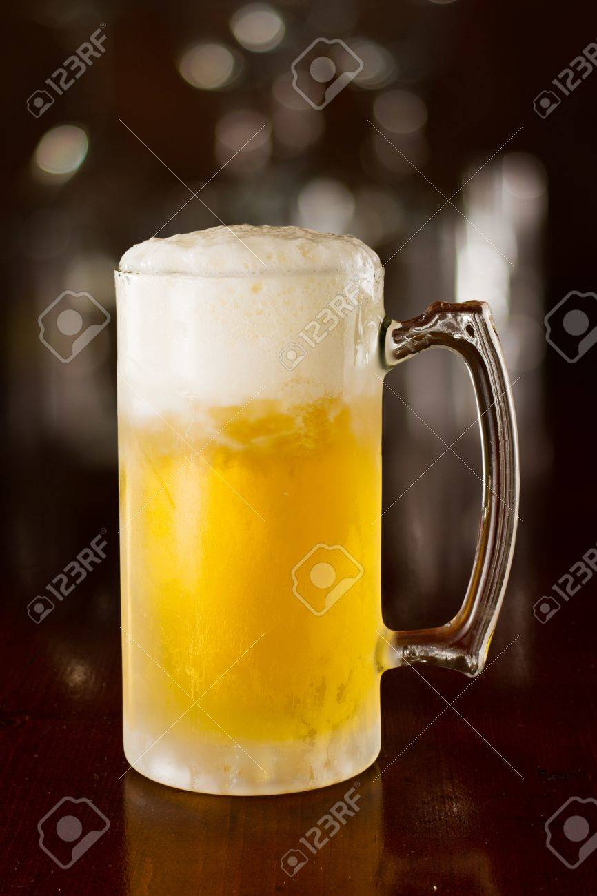 cold beer in a chilled mug served on a busy bar top Stock Photo - 19057775
