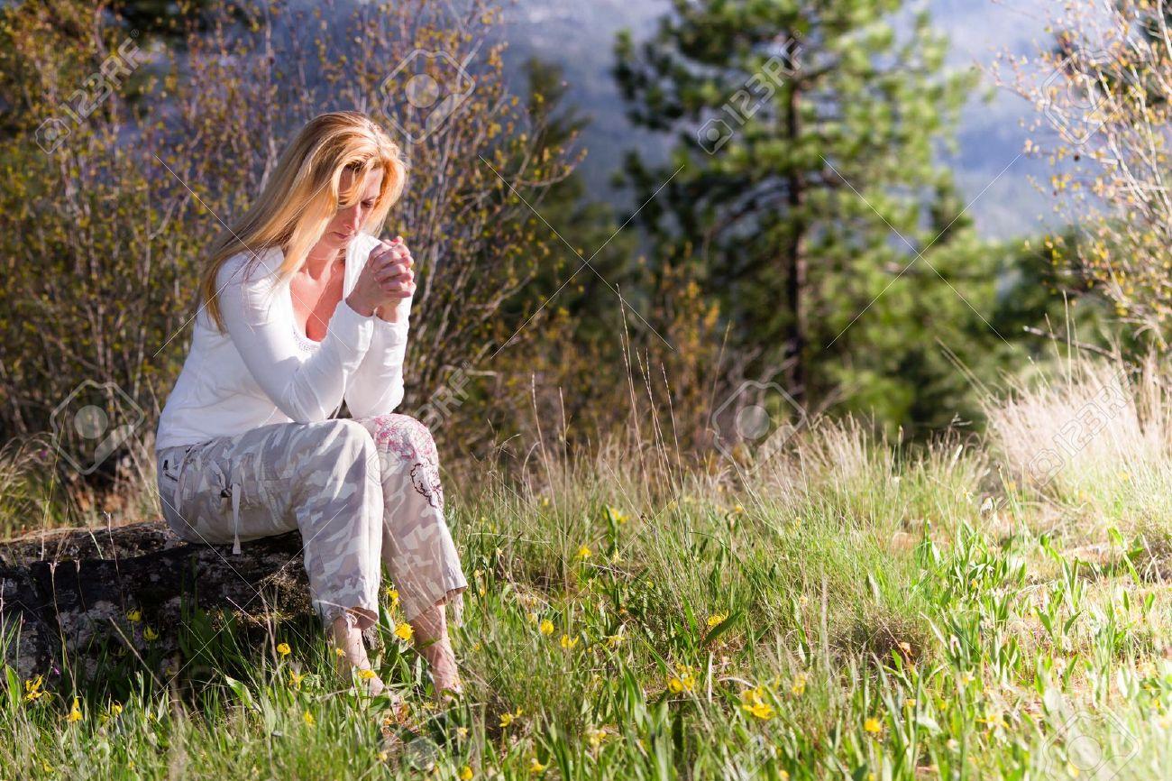 Qui n'a pas connu un jour la solitude et le sentiment d'être abandonné(e) ? 19504593-beautiful-woman-sitting-on-a-rock-praying-with-wild-spring-flowers-around-her-Stock-Photo