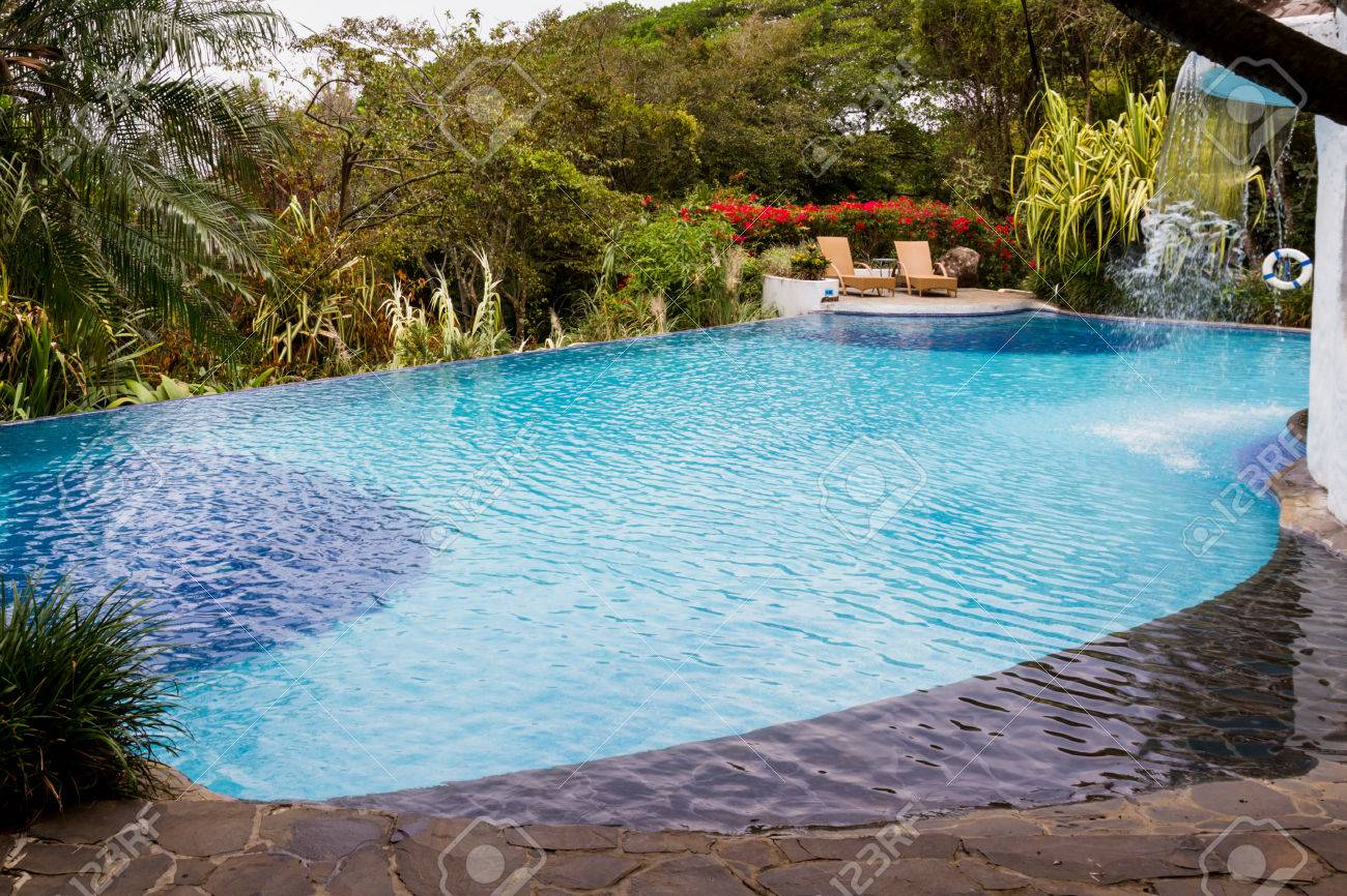 relaxing swimming pool with a waterfall in a tropical rain forest