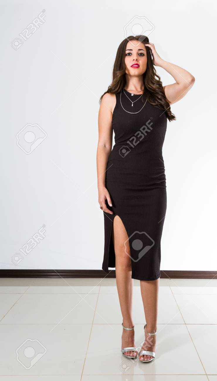 358d65a96206 beautiful young Costa Rican woman wearing a sexy black dress over a white  background Stock Photo