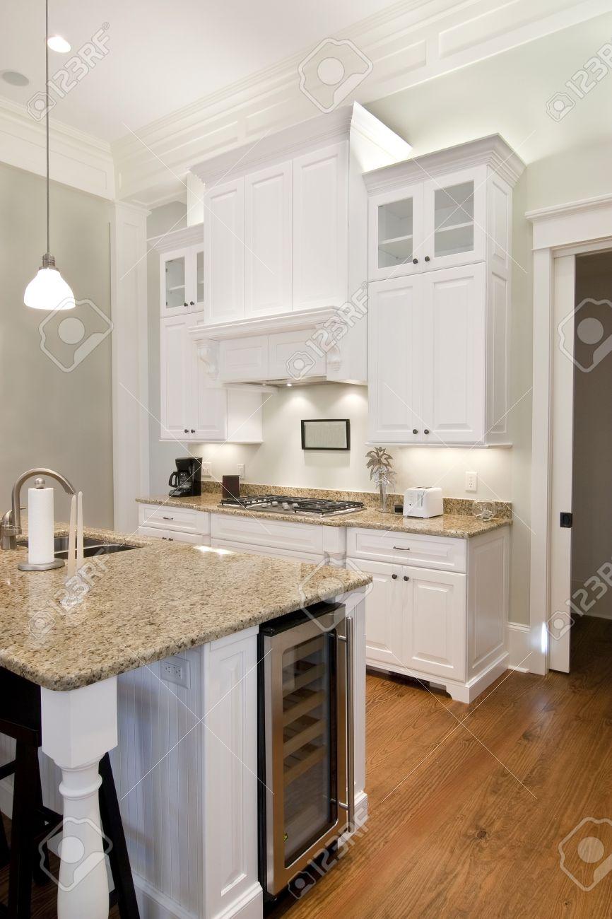Opulent White Kitchen With Granite Countertops And Wine Fridge Stock ...