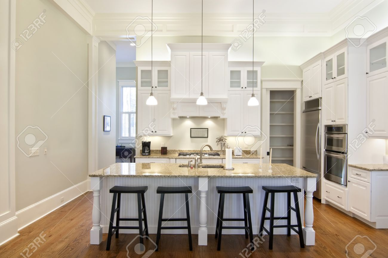 Luxury Eat-in Kitchen With White Cabinets And Granite Counters Stock ...