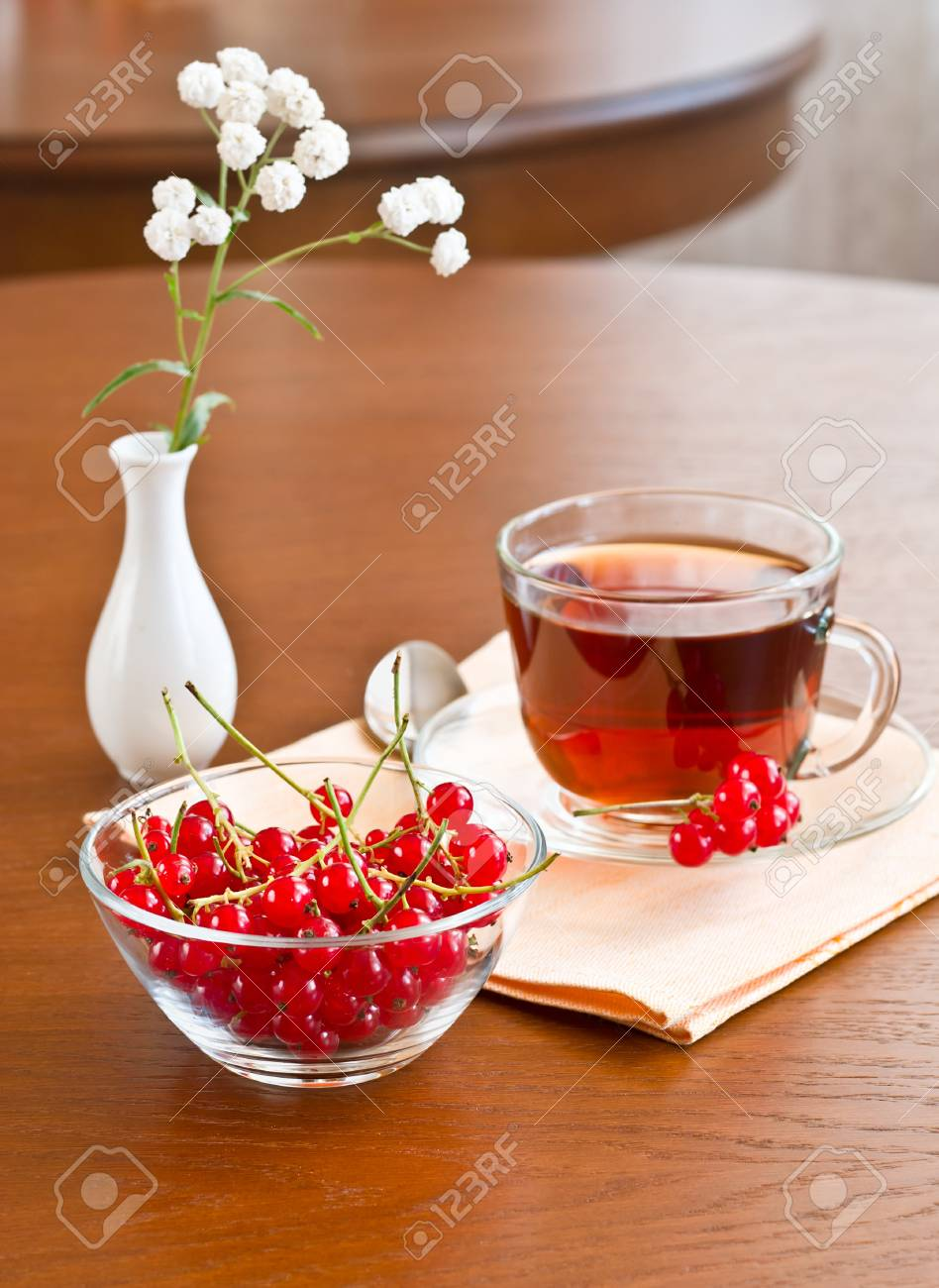 Glass tea cup and redcurrants in bowl on wooden table Stock Photo - 11852542
