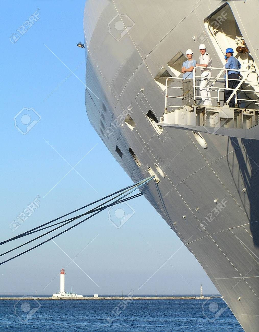 Seamen on a nose big of a cruise vessel, on a background of the sea and a beacon Stock Photo - 1703521