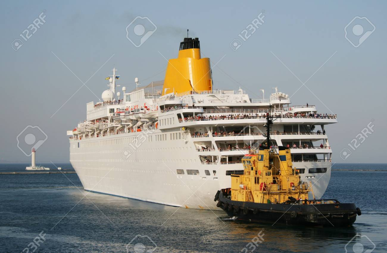 The tow helps to a vessel to leave port water area Stock Photo - 4887320