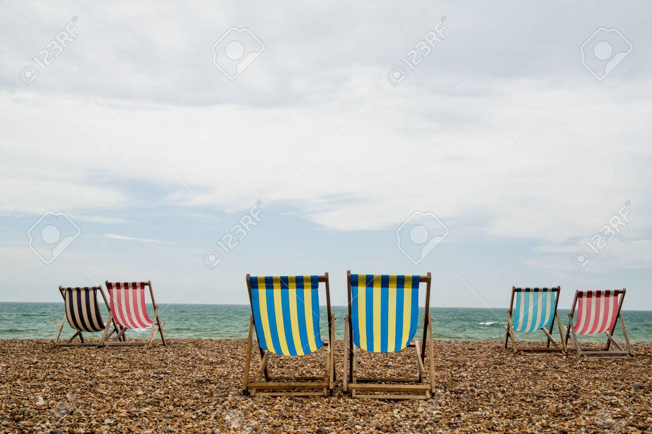 6 stripy deck chairs on a shingle beach in Brighton, Southwest England  Taken on an overcast day Stock Photo - 25475673