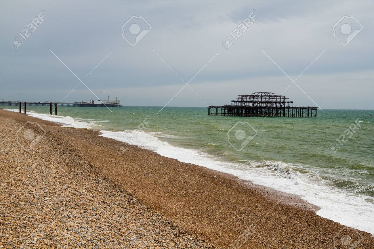 Landscape shot of the ruins of the West Pier on Brighton Beach with the shingle beach in the foreground and Palace Pier in the background Stock Photo - 25475674
