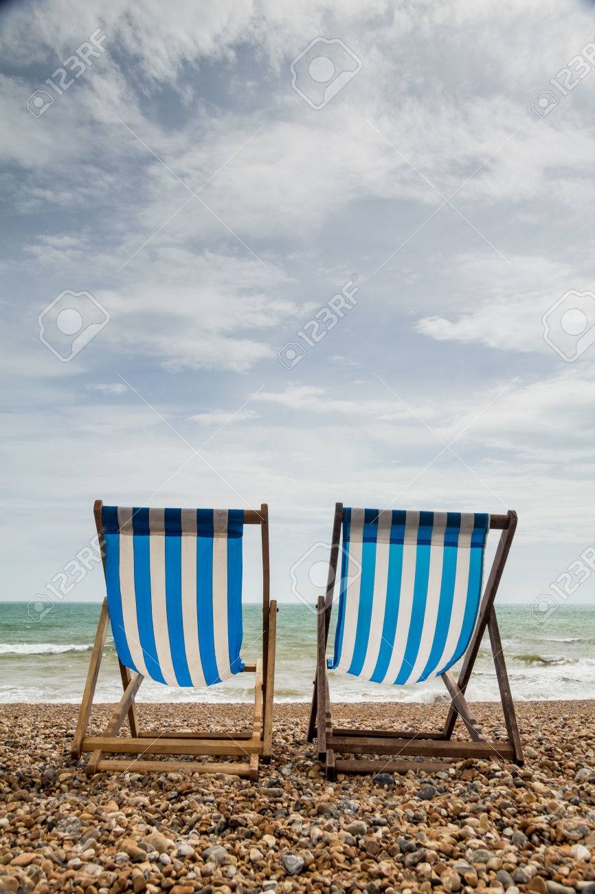 Portrait shot of 2 stripy blue and white deck chairs on a shingle beach in England looking out to sea Stock Photo - 25475639
