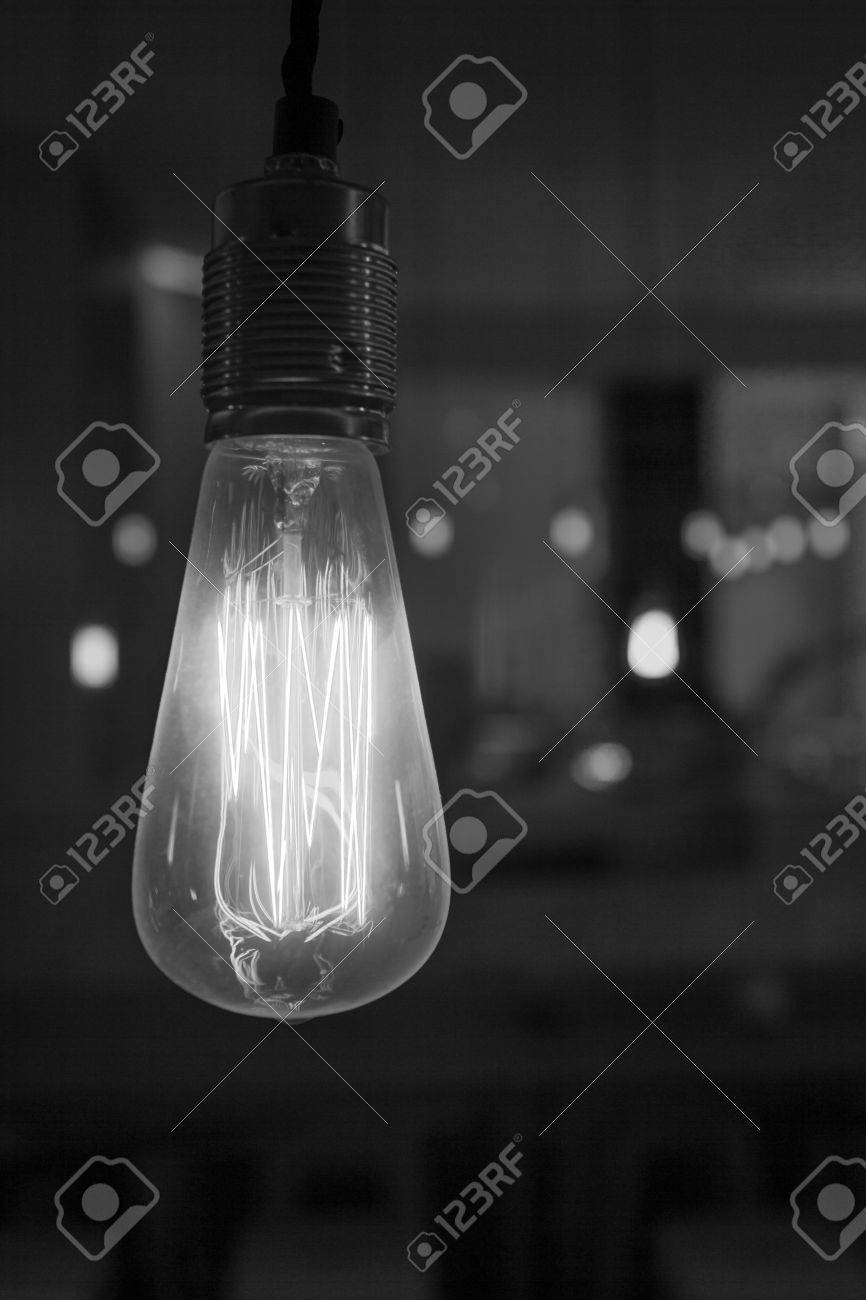 Glowing lightbulb dangling from the ceiling in black and white Stock Photo - 29479863