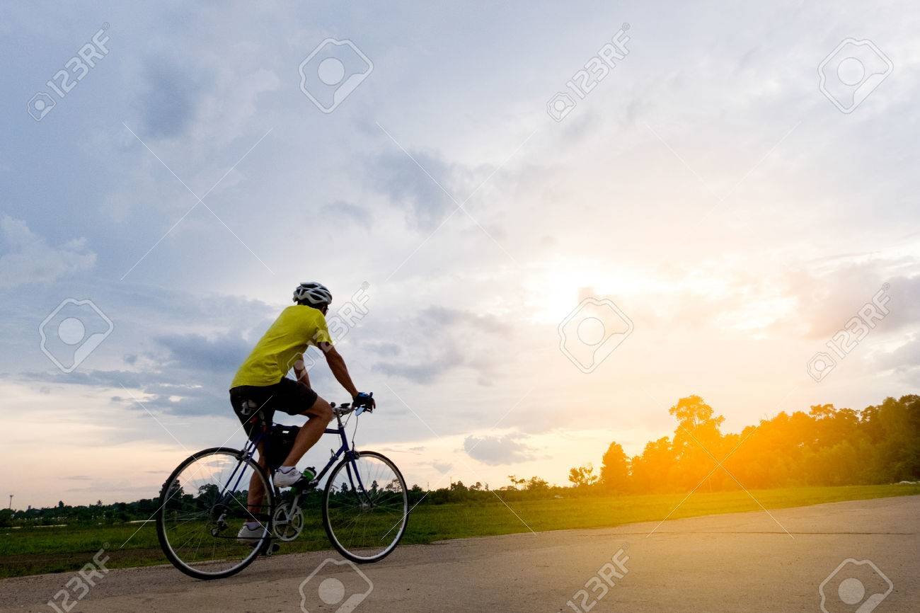Cyclist in motion on background beautiful sunset with silhouette
