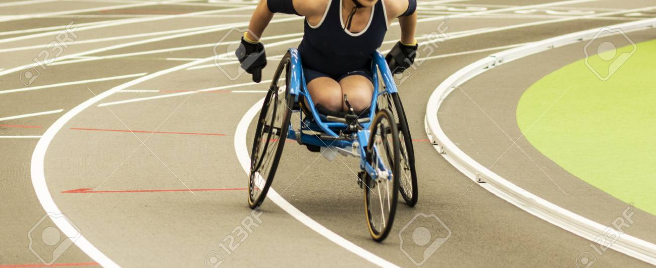 A high school girl in a wheelchair is racing the mile on an indoor track. - 120505305