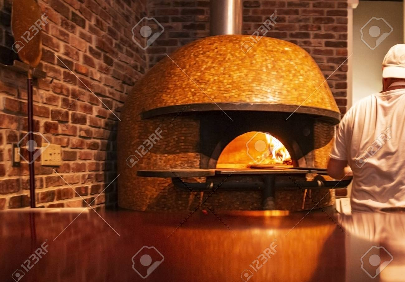 A chef is putting an uncooked pizza in to the high heat of a brick oven pizza oven. - 120505308