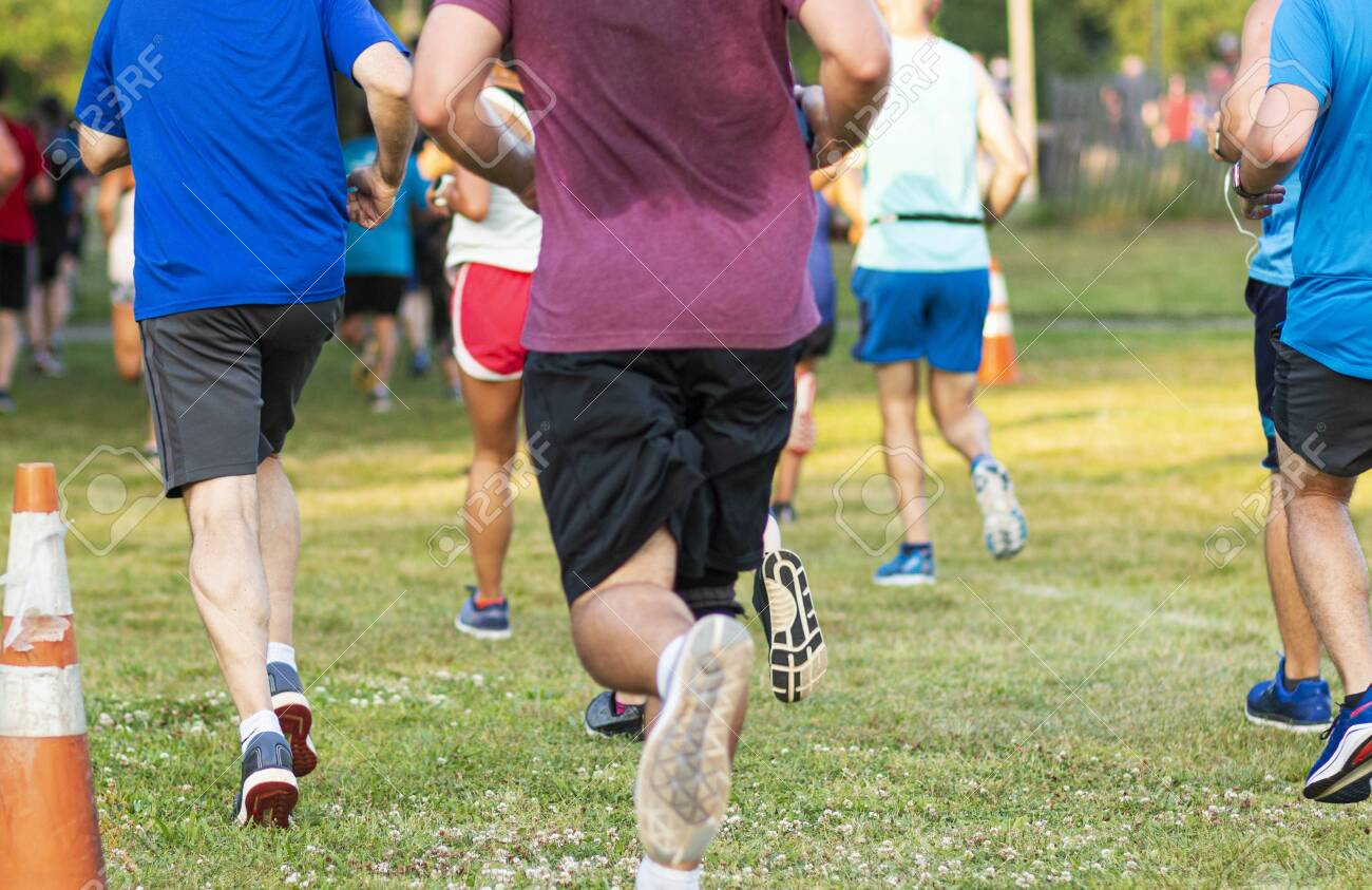 Close up of rear view of many runners racing a 10K at Sunken Meadow state park on the grass. - 135755813
