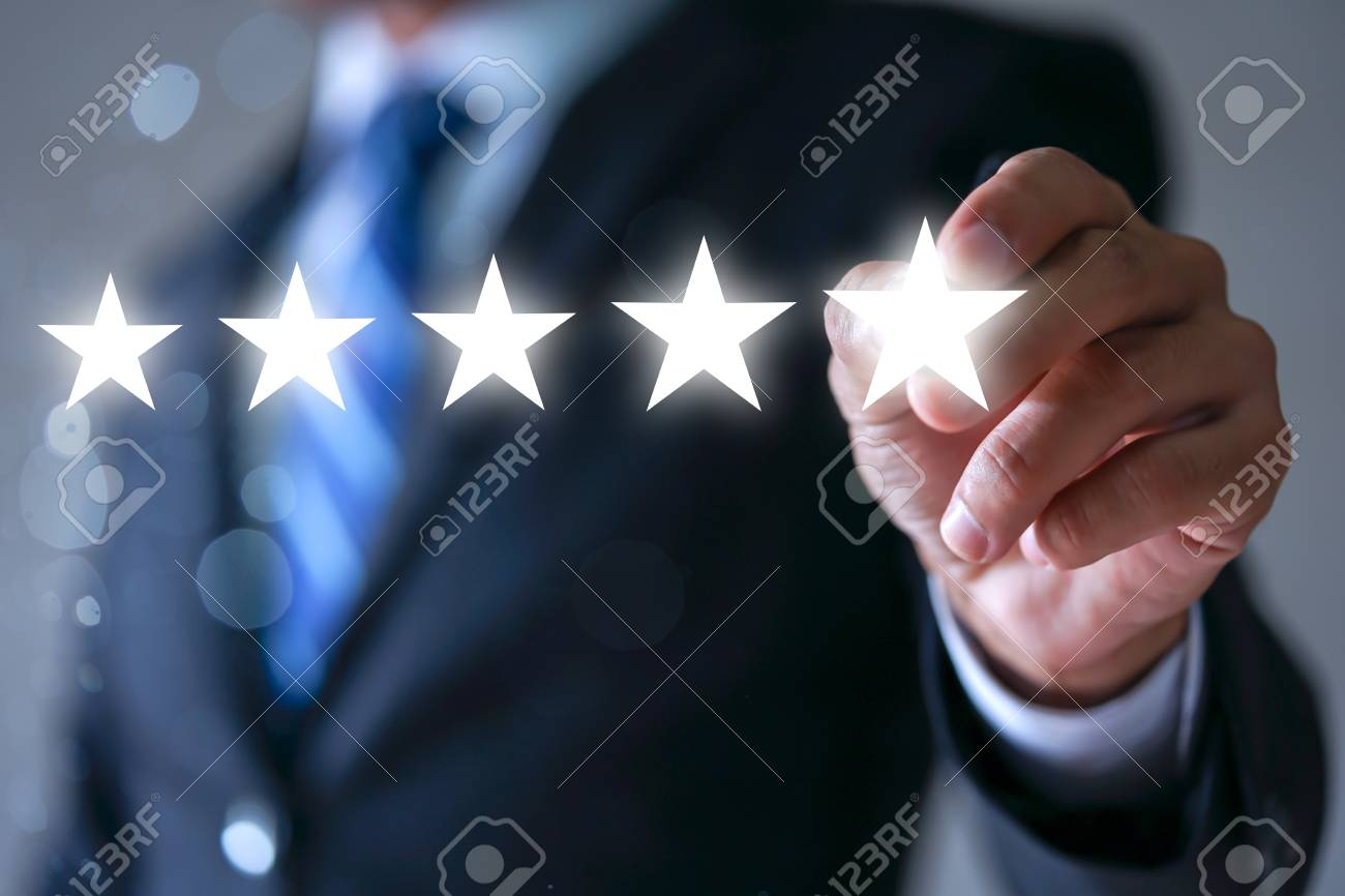 Businessman pointing five star symbol to increase rating of company - 95475990
