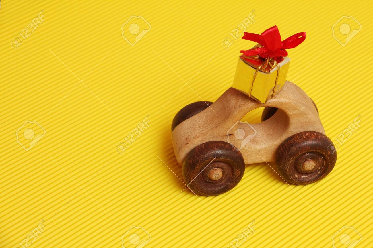 Wooden Car Toy And Golden Gift Box With Red Ribbon On The Roof