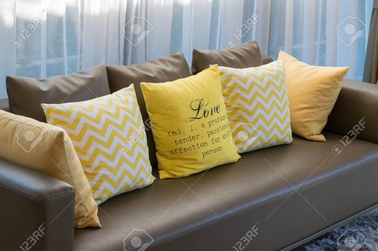 modern living room design with brown sofa and yellow pillows