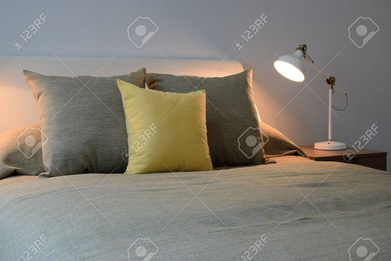 Gemütliches Schlafzimmer Interieur Mit Kissen Und Leselampe Auf Dem ...