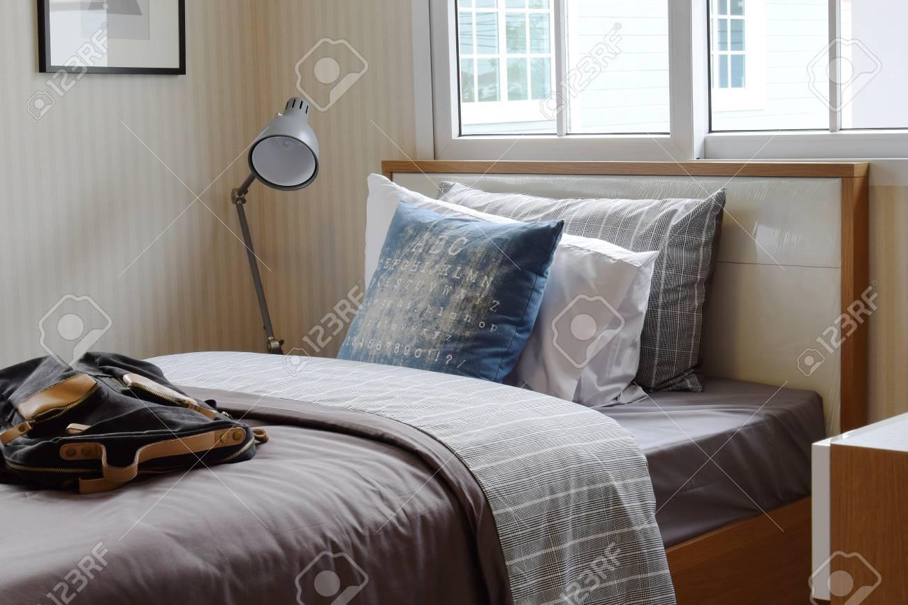 Interno accogliente camera da letto con cuscini e lampada da