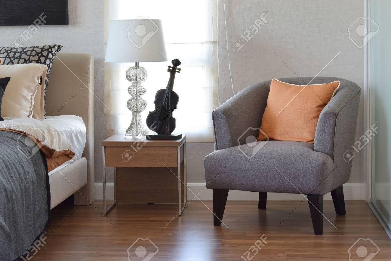 Moderna sovrum inredning med orange kudde på grå stol och ...