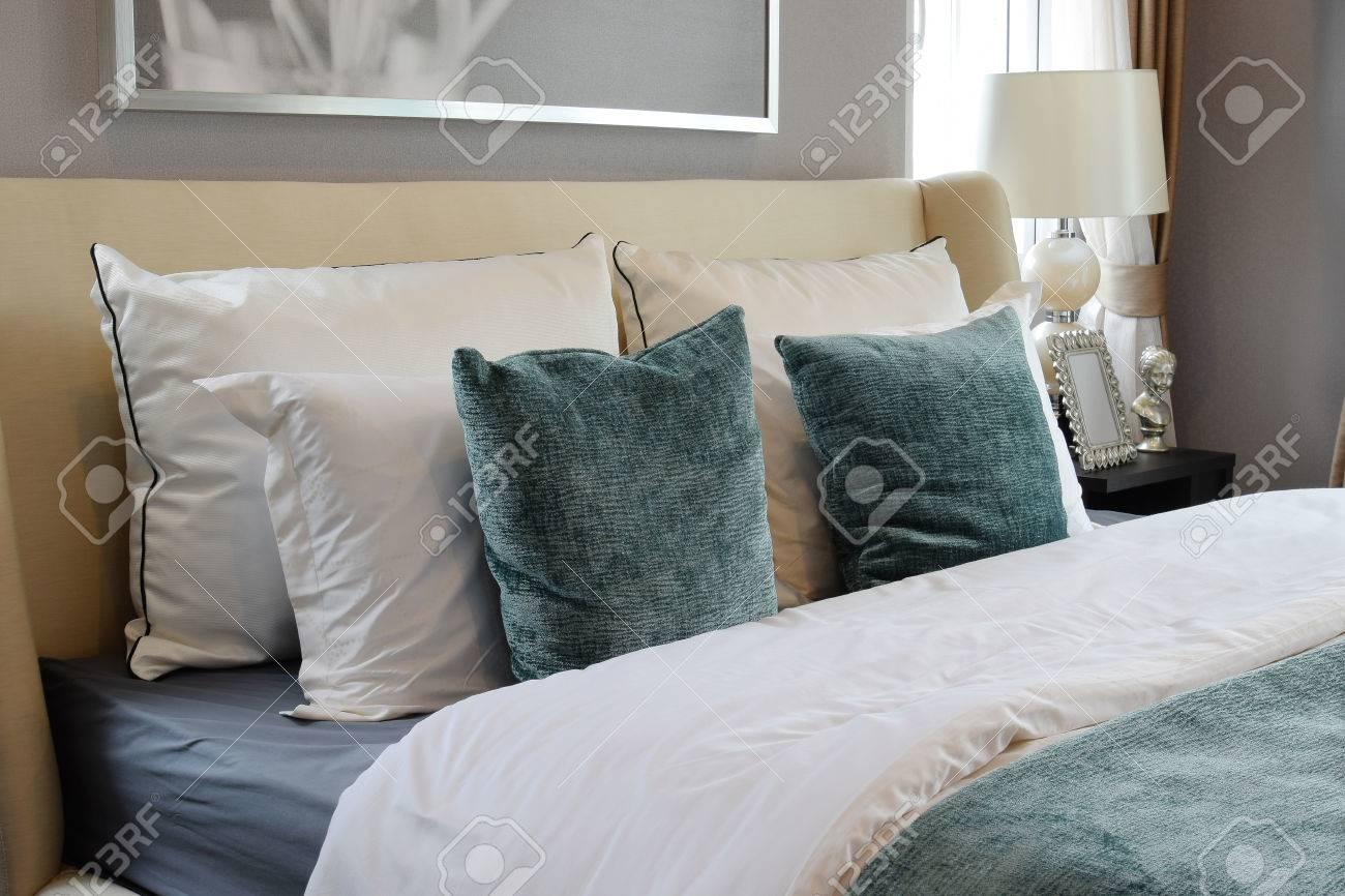 Camera da letto, tra design con cuscini bianchi e verdi su letto bianco e  lampada da tavolo decorativa.