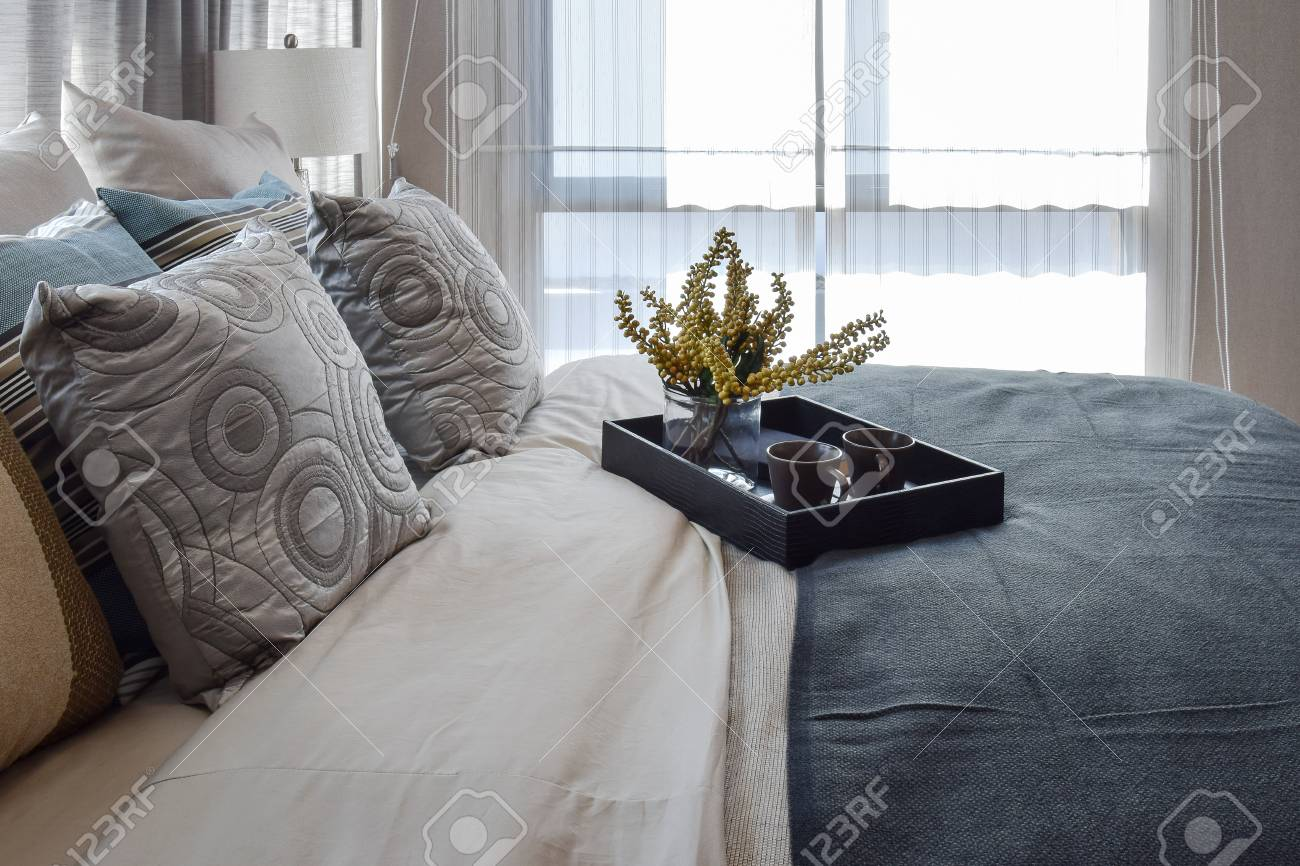 Camera da letto interior design di lusso con cuscini a righe e decorativi  insieme di tè sul letto