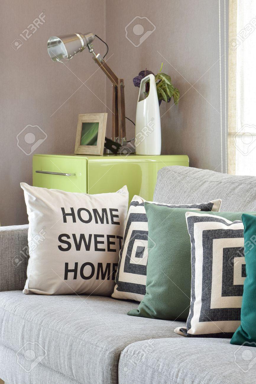 Canapé gris confortable avec des oreillers de modèle de la géométrie dans  le salon moderne