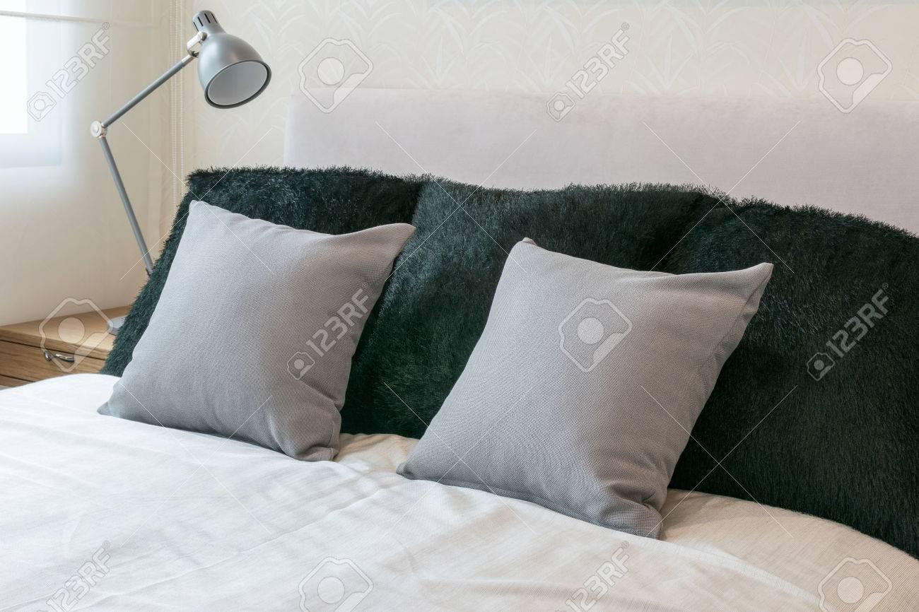Chambre design d\'intérieur avec des oreillers sur le lit gris blanc et  lampe de table décorative.