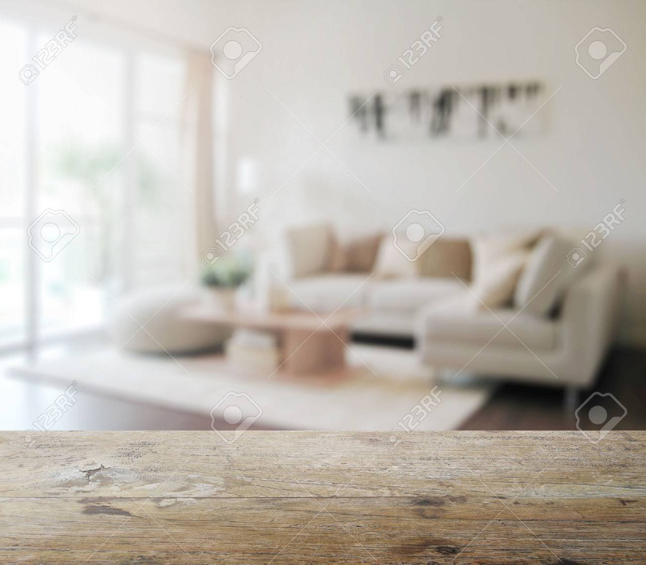 wooden table top with blur of modern living room interior as..