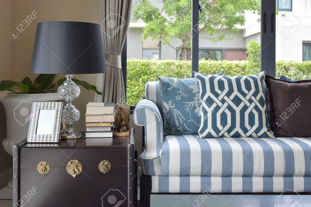 blue pattern pillows on striped sofa with black lamp in living..