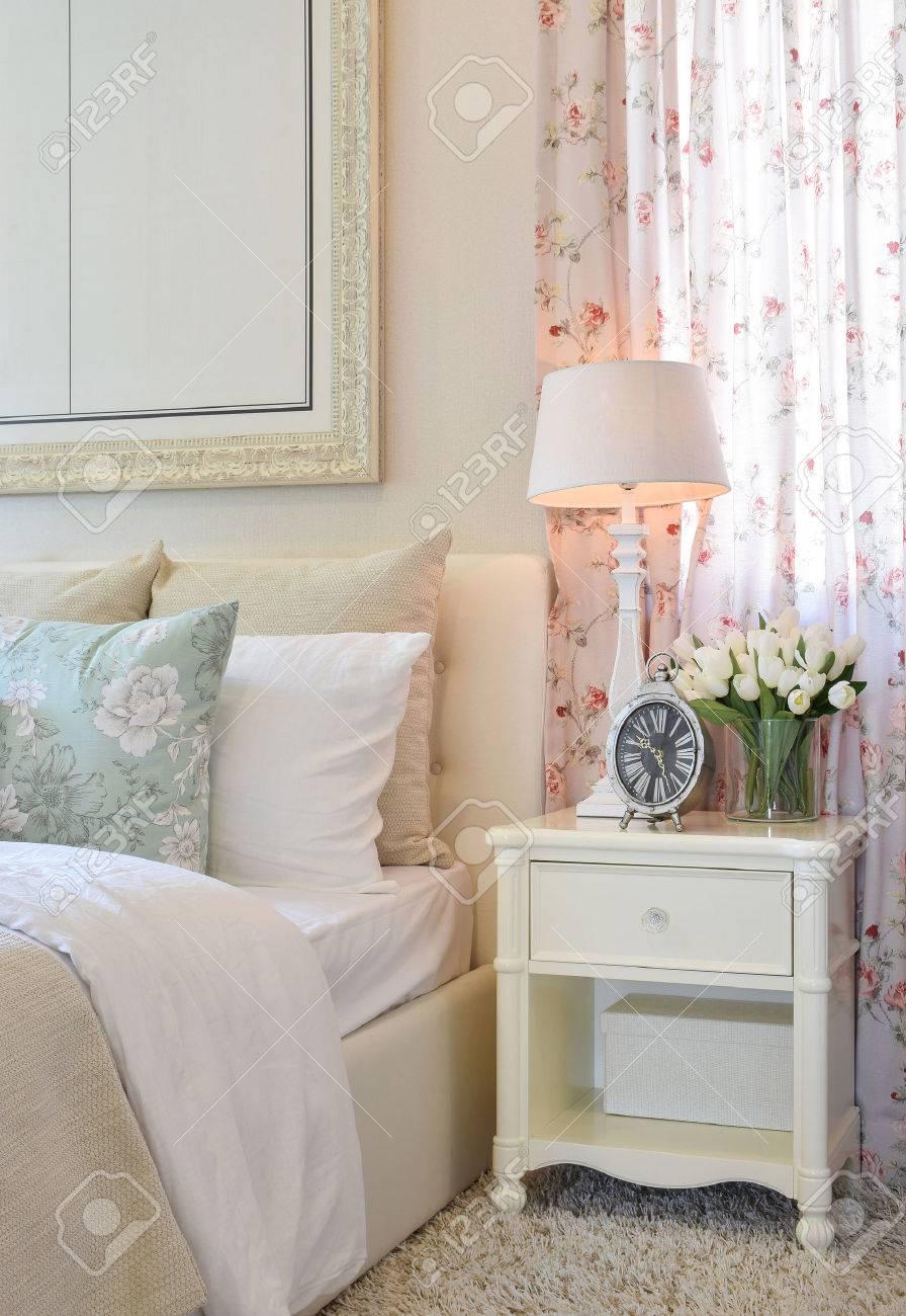 Intérieur de la chambre vintage avec lampe décorative de table, réveil et  fleurs sur la table blanche