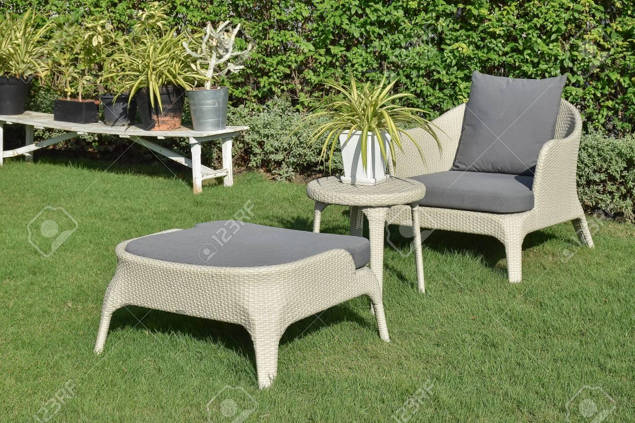 Jardin verdoyant avec un groupe de salon de mobilier d\'extérieur avec des  chaises en rotin, canapé et table