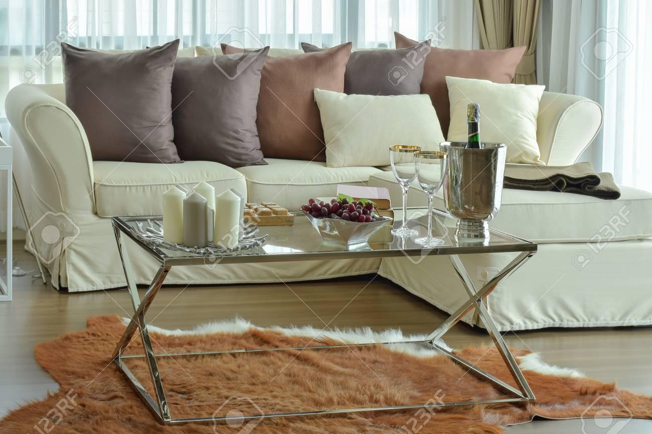 Bougies aromatiques et verres à vin sur la table avec canapé beige et  oreillers marron profond dans le salon moderne