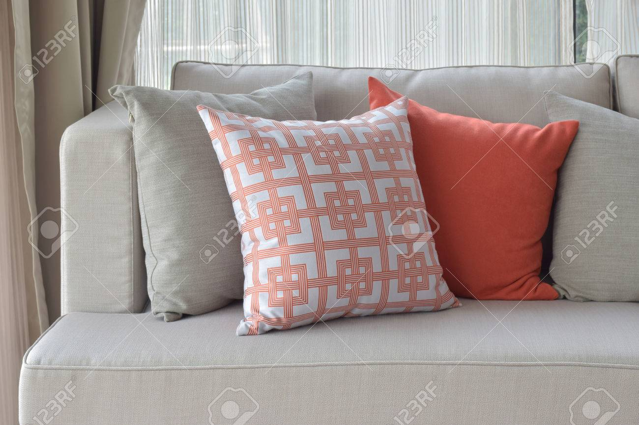 Chinese pattern in orange with deep orange and gray pillows on..