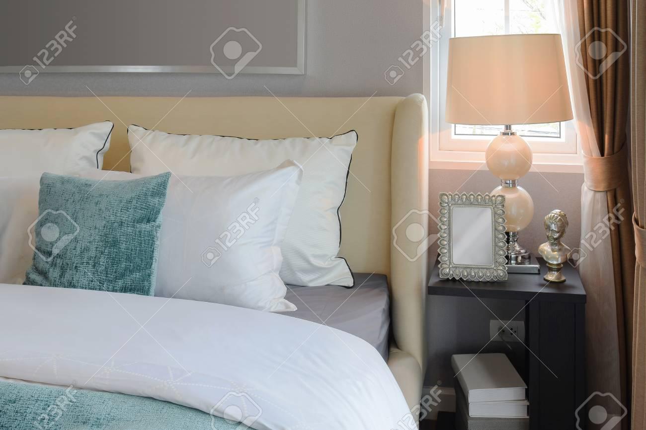 Interior design camera da letto con cuscini bianchi e verdi sul letto  bianco e lampada da tavolo decorativa.