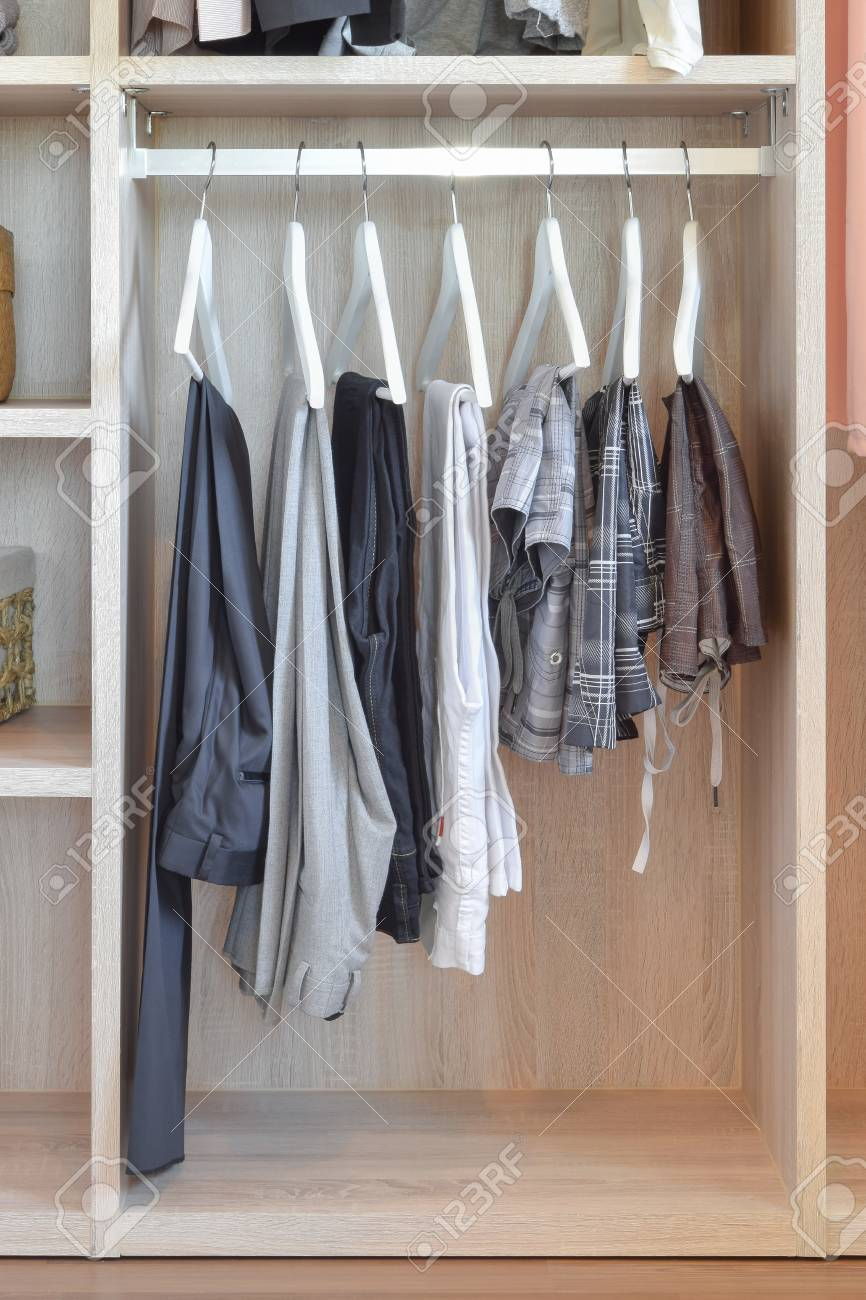 Modern Closet With Row Of Pants Hanging In Wooden Wardrobe Stock