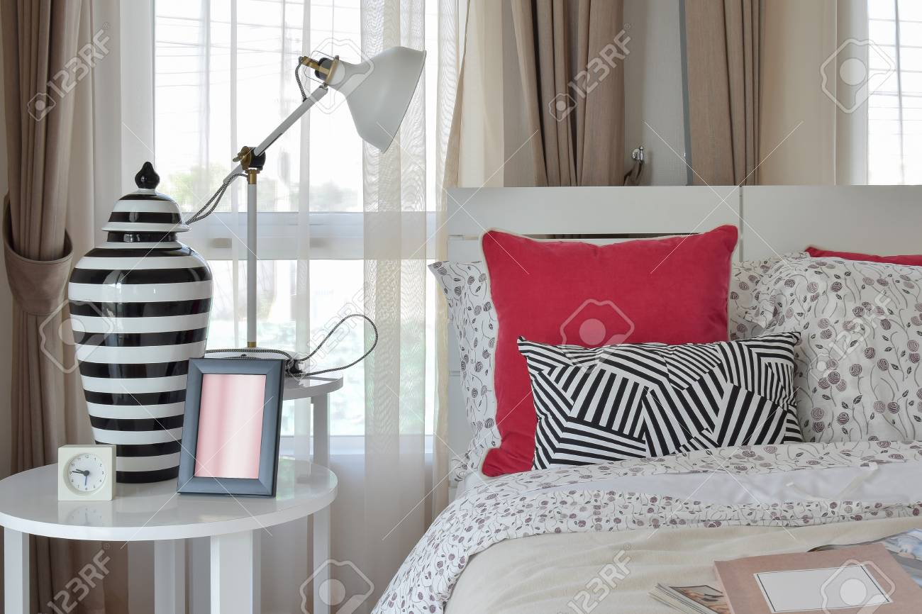 Interni eleganti della camera da letto con cuscini con motivo floreale e  lampada da tavolo decorativa