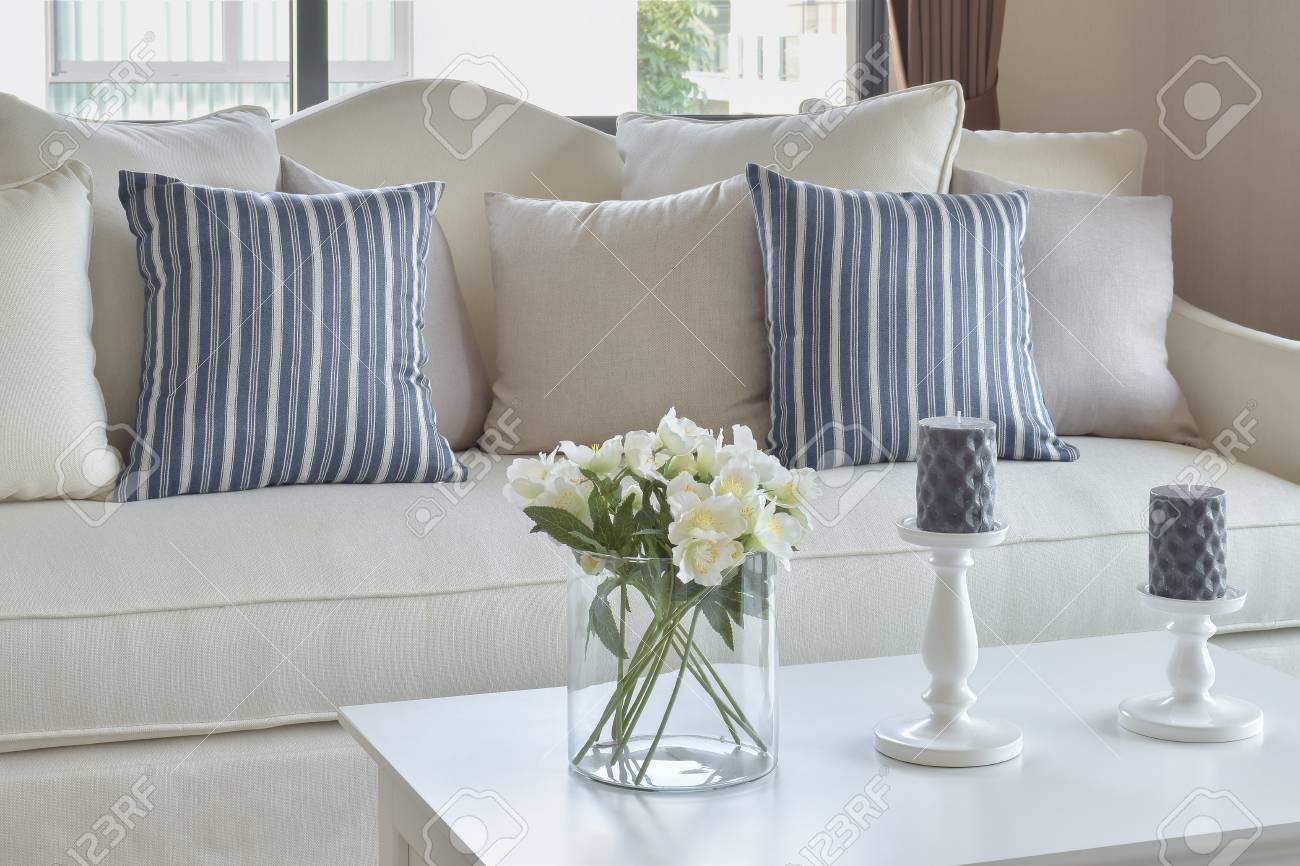 blue striped pillows on a casual sofa and decorative flower in..