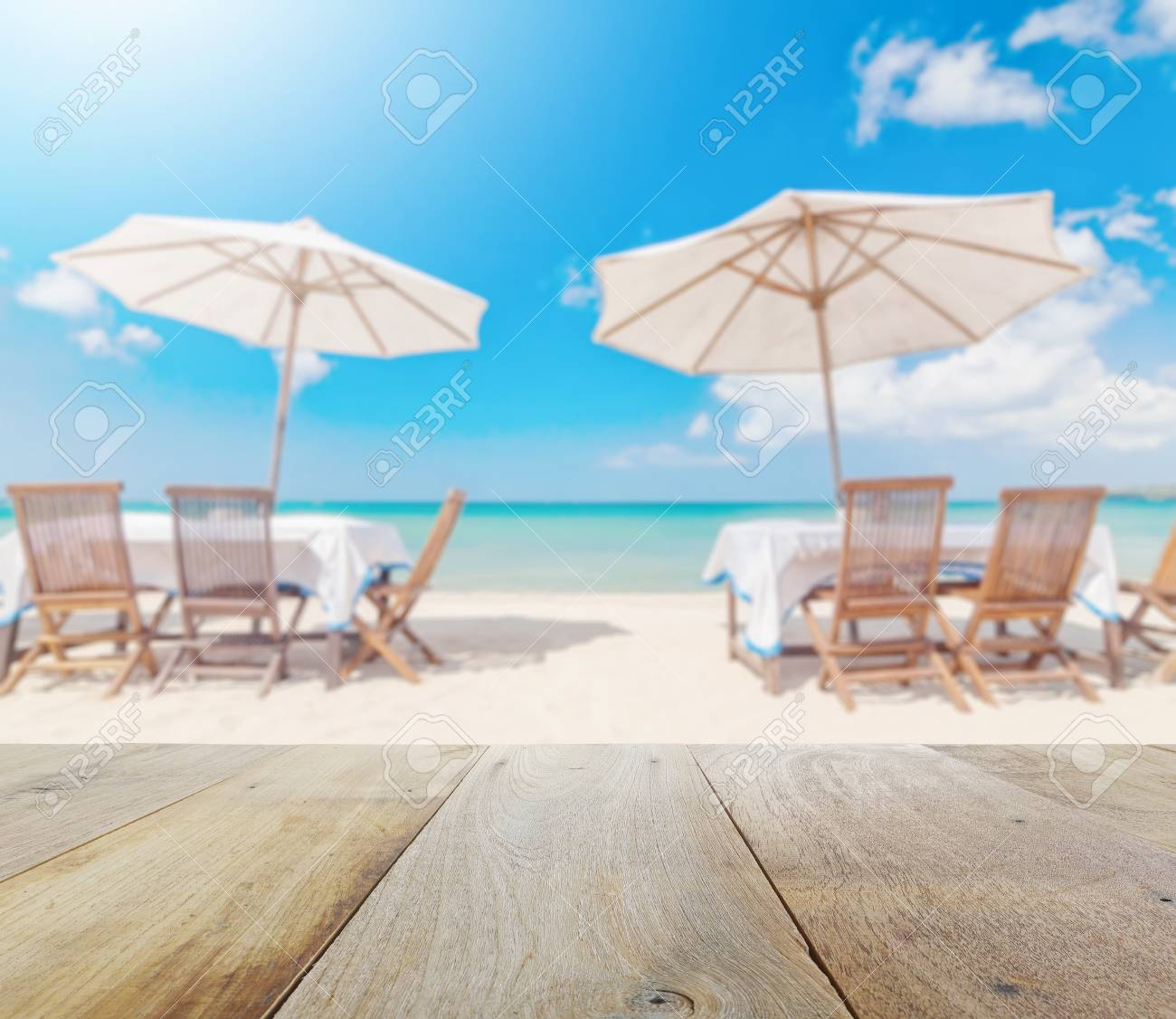 Stock Photo   Wooden Table Top With Blur Of Table Set And Umbrella On The  Beach