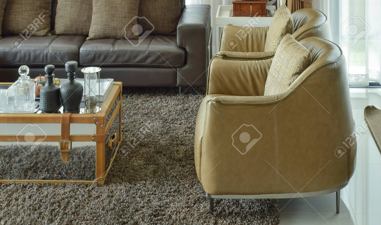 Light brown leather armchairs and dark brown leather sofa in..