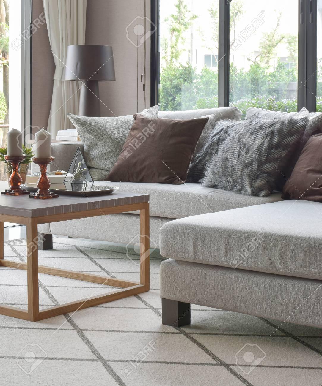 Banque Du0027images   Oreillers Marron Et Gris Sur Un Canapé Beige Et Table En  Bois Dans Un Salon Moderne