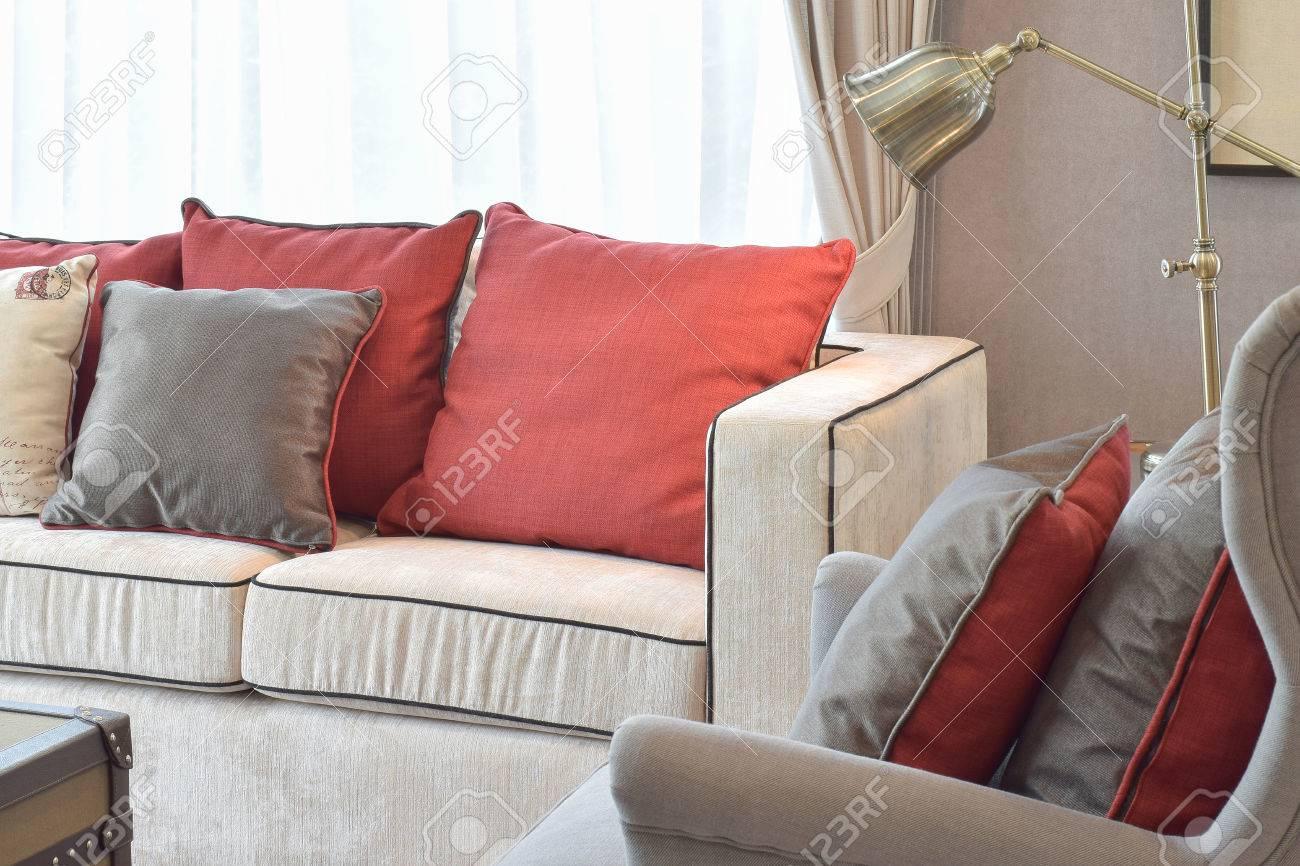 Salon de style industriel classique avec canapé beige et oreillers lénine  rouge et marron avec lampe de lecture en laiton