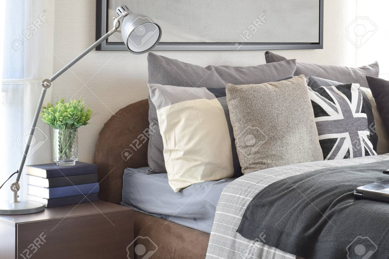 Camera da letto moderna con cuscino grigio e lampada sul comodino in legno  a casa