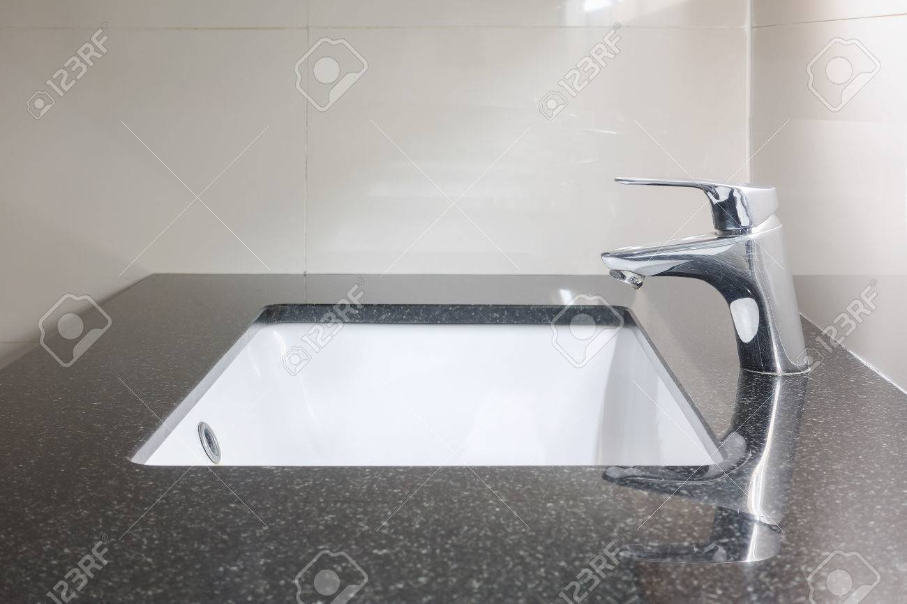 under counter lavatory with black granite top and faucet stock photo