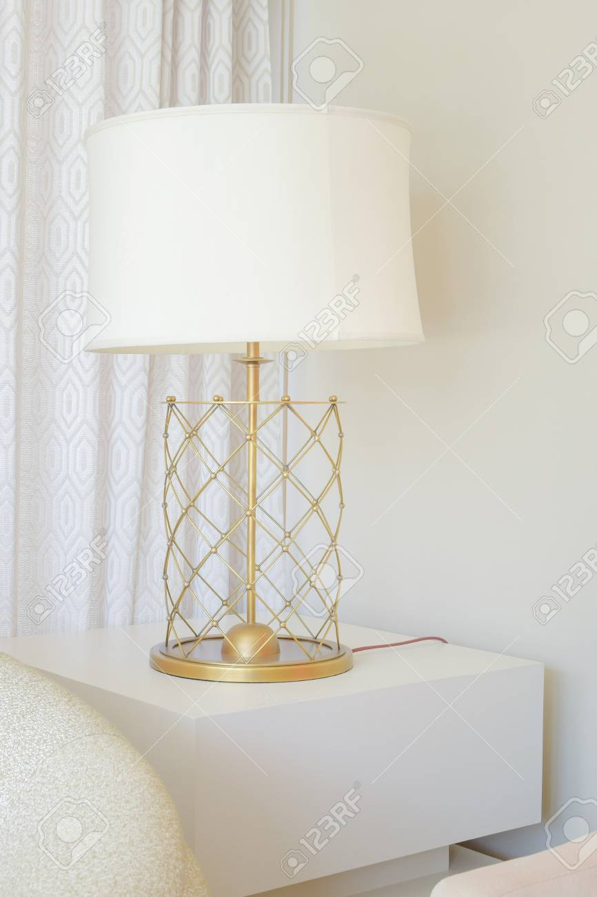 White Shade Table Lamp With Brass Base At The Corner Of Living