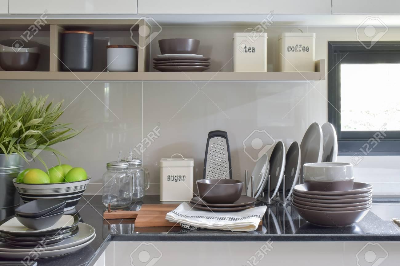 Piatti e ciotole in ceramica sul bancone e mensola nella cucina moderna